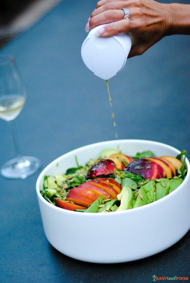 Pouring a homemade dressing over a peach and avocado salad