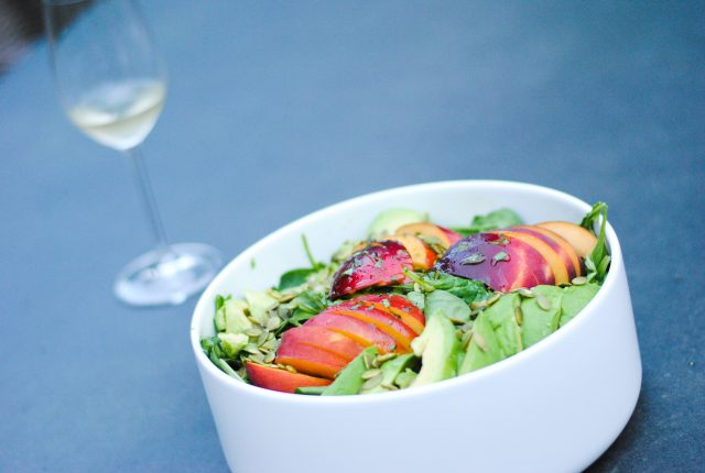 peach avocado salad with homemade dressing and a glass of white wine