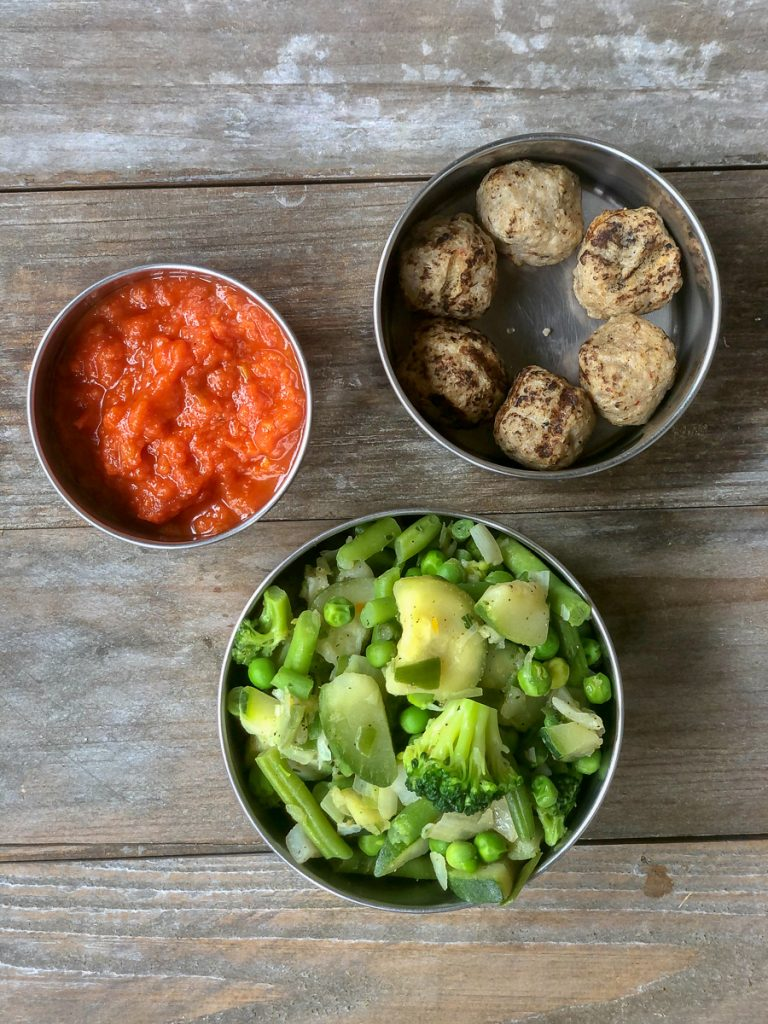 Cooked mixed greens and meatballs with marinara sauce