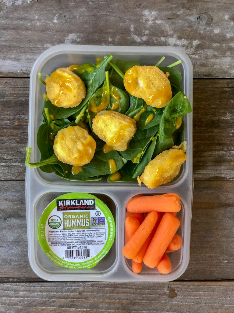 GF chicken nuggets on top of spinach with honey mustard dressing, carrots, mini hummus - easy costco lunches