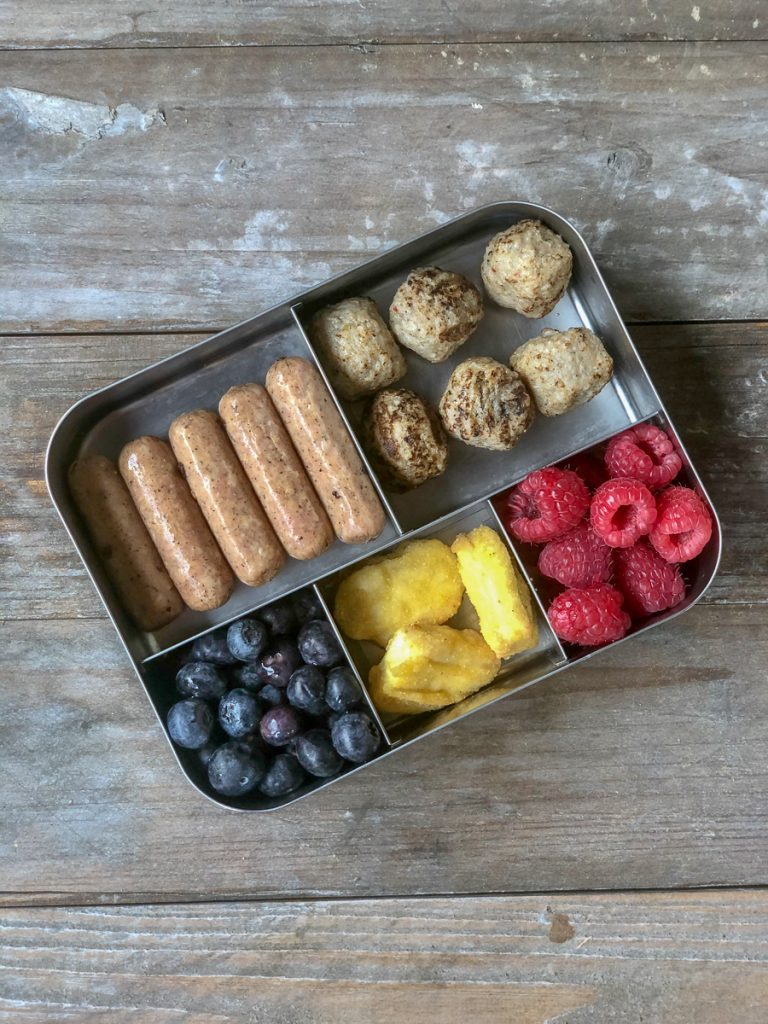 variety of sausage, chicken nuggets, and meatballs with blueberries and raspberries
