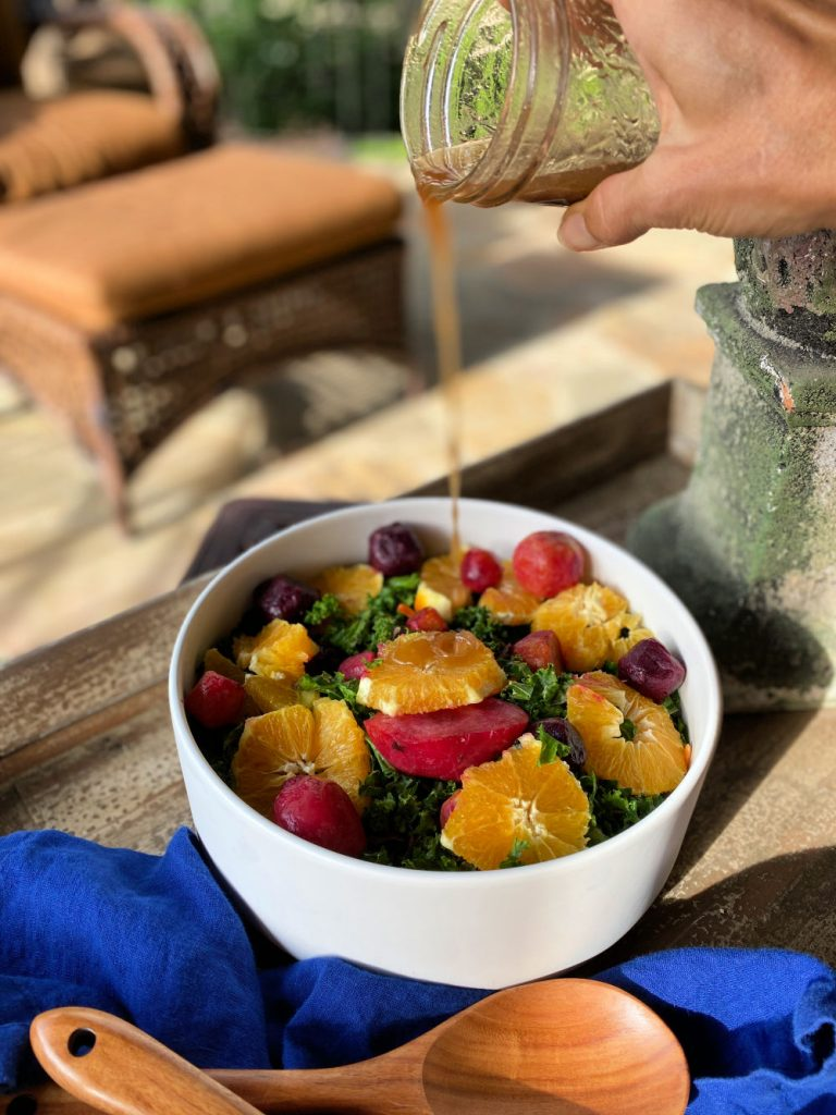 pouring orange balsamic dressing on kale salad