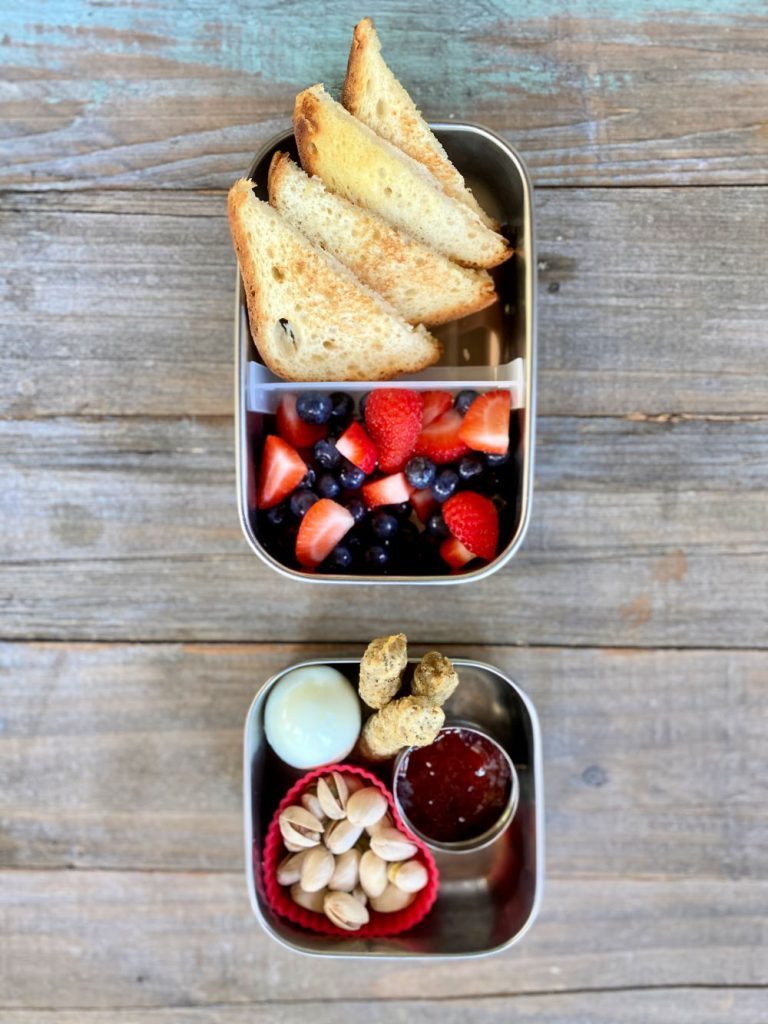 Hard boiled egg, chicken sausage, gluten-free toast, fruit salad, pistachios, jelly school lunch