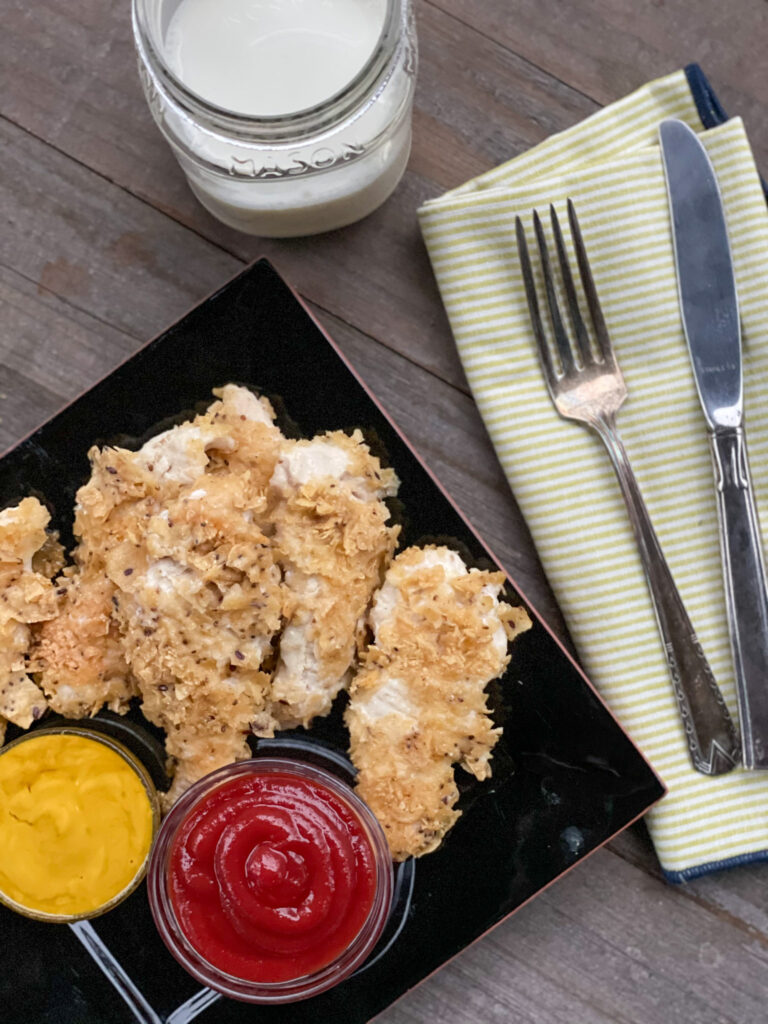 baked chicken tenders on a plate with 2 dipping sauces